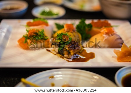 Japanese sushi platter with salmon, eel (unagi), yellow tail (hamachi), sea eel (anago), engawa, salmon roe (ikura), ginger and wasabi. Shallow DOF to focus on the highlight unagi sushi - stock photo