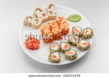 Japanese sushi & roll set on a white plate with ginger and wasabi - stock photo