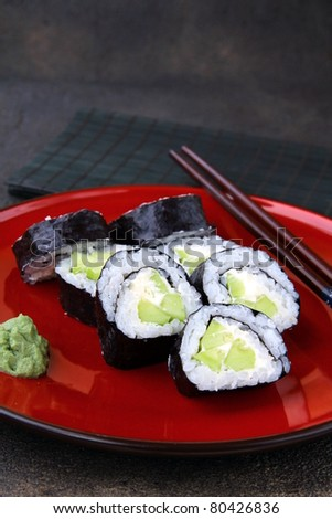 Japanese sushi rolls with cucumber with wasabi and chopsticks - stock photo