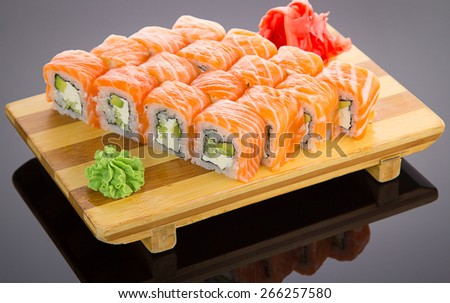Japanese tasty sushi set on a wooden plate over black background - stock photo