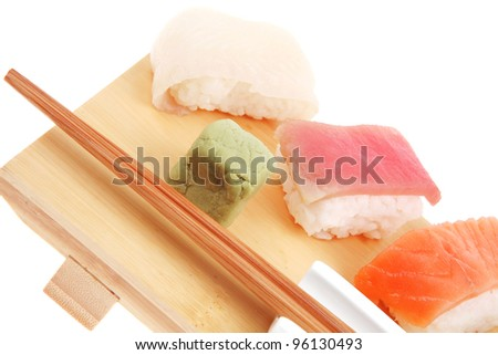 Japanese traditional cuisine - Set of Tuna (maguro) Salmon (sake) and Eel (unagi) Nigiri Sushi  with Wasabi  and chopstick on wooden plate isolated over white background