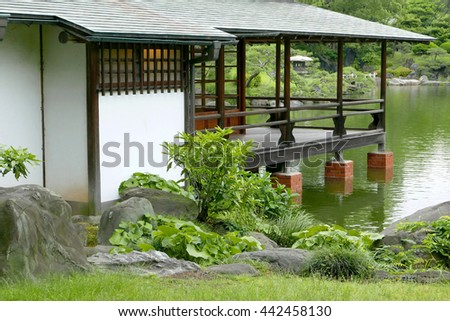 Japanese traditional pavilion building and water pond in the zen garden