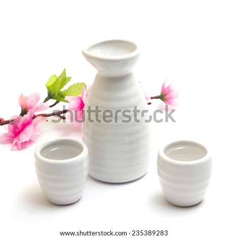 japanese traditional sake cups and bottle with sakura , sake is a japanese liquor made from fermented rice. Isolated on white background.