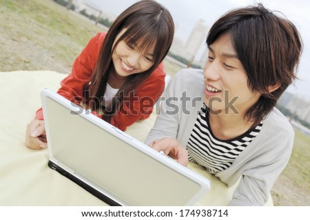 Japanese University student couple looking at laptop
