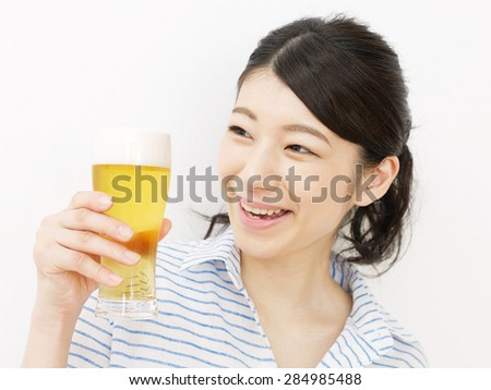 Japanese woman drinks the beer - stock photo