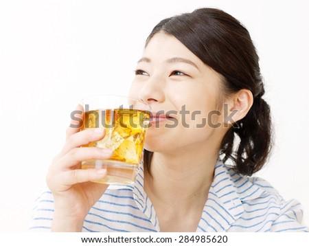 Japanese woman drinks the iced tea - stock photo