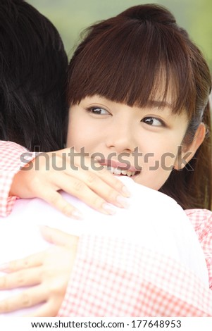 Japanese woman hugging a Japanese man in the park