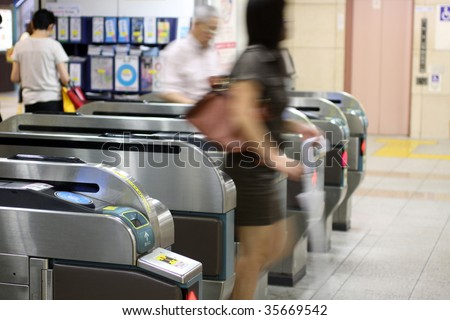 Japanese woman leaving a subway ticket gate in Tokyo, Japan