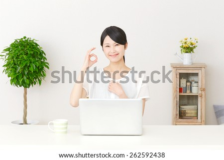 Japanese woman OK gesture with PC - stock photo