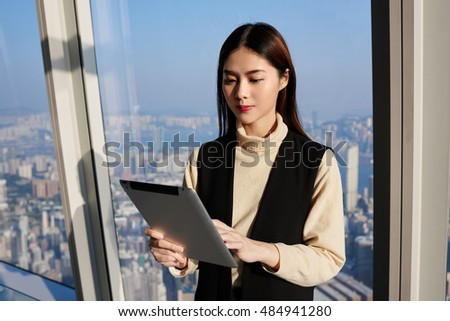 Japanese woman professional worker in real estate company is reading advertising in internet via digital tablet, while is standing in modern office interior near window with view of business district