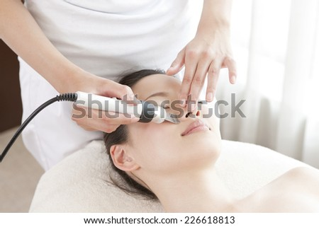 Japanese woman receiving face treatment