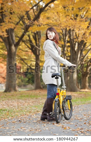 Japanese woman riding a bicycle is looking back, smiling,