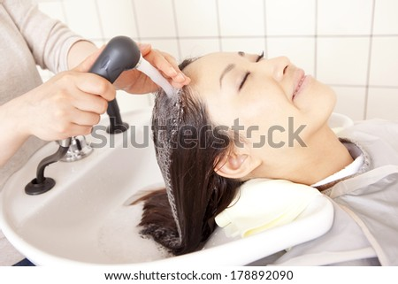 Japanese woman shampooing hair in salon