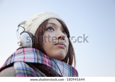 Japanese woman smiling while listening to music