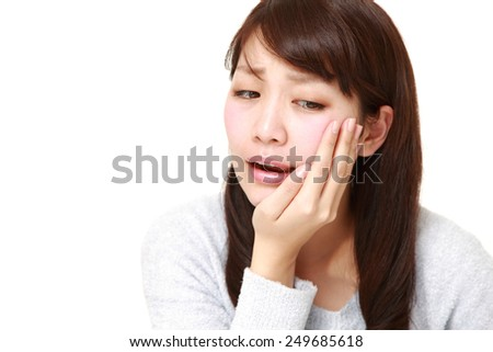 Japanese woman suffers from toothache - stock photo