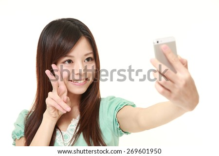 Japanese woman takes a selfie - stock photo