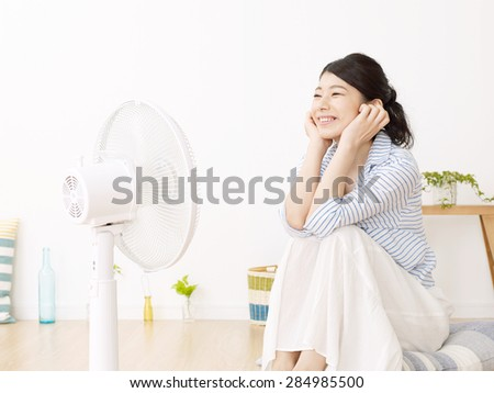 Japanese woman uses the electric fan - stock photo