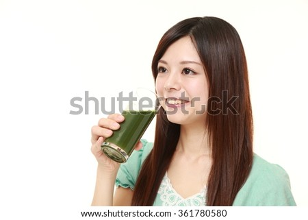 Japanese woman with green vegetable juice - stock photo