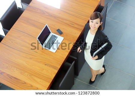 Japanese worker standing in boardroom - stock photo