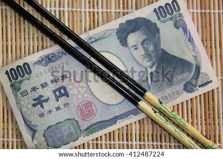 Japanese yen banknote with chopsticks - stock photo