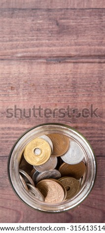 Japanese Yen coins in a mason jar over wooden background