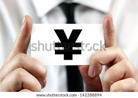 Japanese Yen sign. Businessman in white shirt with a black tie, shows business card - stock photo
