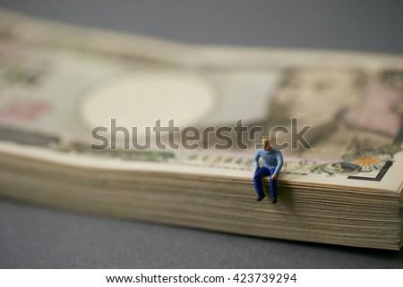 Japanese yen stash and miniature men - stock photo