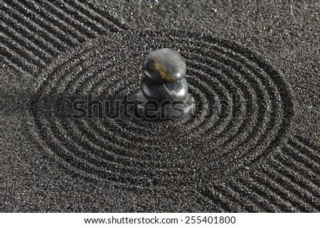 Japanese ZEN garden with stacked stones in black sand - stock photo
