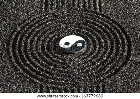 Japanese ZEN garden with stone of yin and yang  in raked sand - stock photo