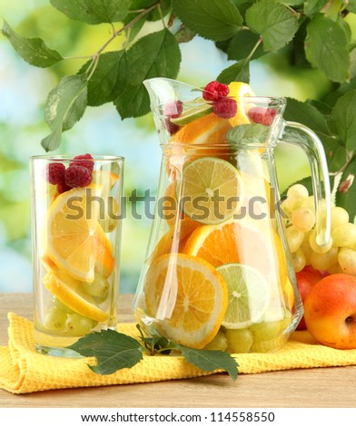 jar and glass with citrus fruits and raspberries, on green background - stock photo