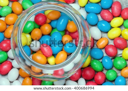 jar full of colorful candies and scattered sweets.view from above.festive background for your design.toned - stock photo