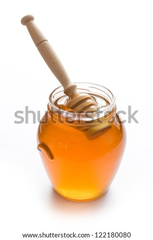 Jar full of honey and stick isolated on white background