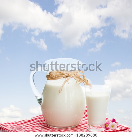 jar  full of milk  and glass in garden in sunny day with blue sky - stock photo