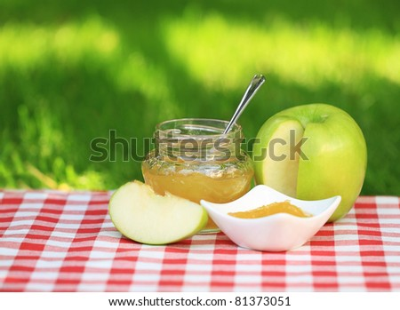Jar of apple jam on the table in the summer garden