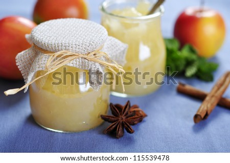 Jar of apple jam with cinnamon and fresh apples