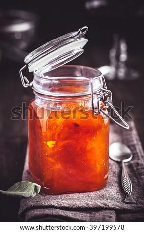 Jar of apricot jam on table closeup - stock photo