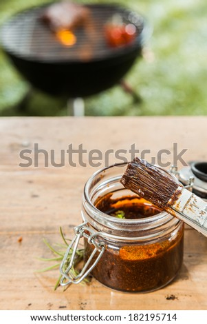Jar of basting sauce and a basting brush standing on a wooden picnic table outdoors for the meat grilling on the BBQ in the background on a green lawn - stock photo