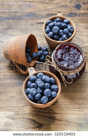 Jar of blueberry jam and bowls of blueberries