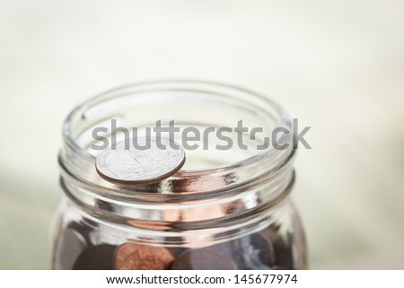 Jar of change with quarter on lip - room for text - stock photo