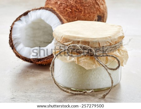 jar of coconut oil and fresh coconut on kitchen table - stock photo