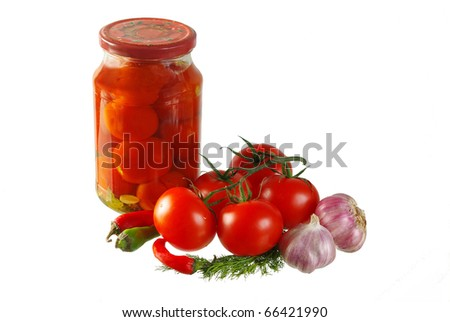 Jar of colorful pickled tomatoes with tomatoes, garlic, pepper