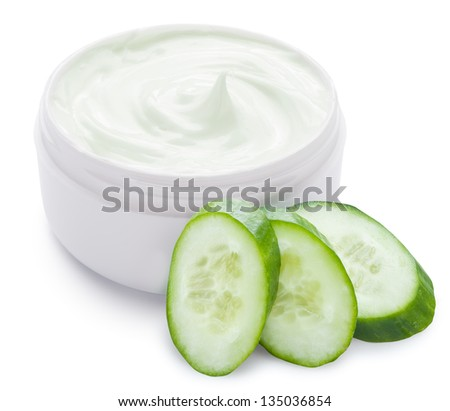 Jar of cream and slices of cucumber on a white background. - stock photo