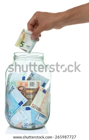 Jar of Euro bills and a hand putting five Euro into it isolated on white. concept.