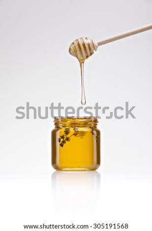 jar of golden honey on a white background with lavender flowers inside - stock photo