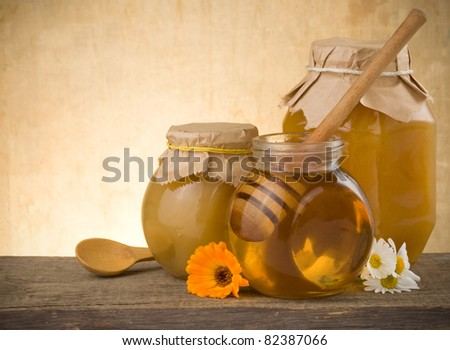 jar of honey and flowers on wood background - stock photo