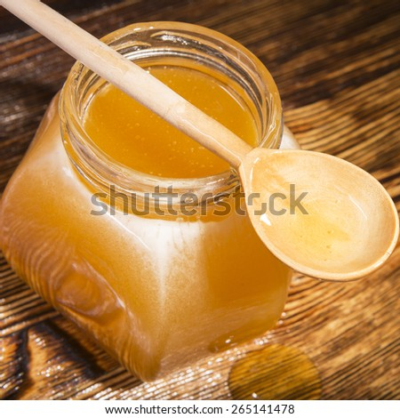jar of honey and spoon on a wooden background