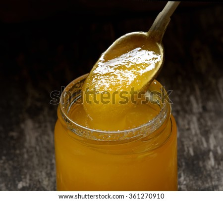 jar of honey and spoon on a wooden background - stock photo