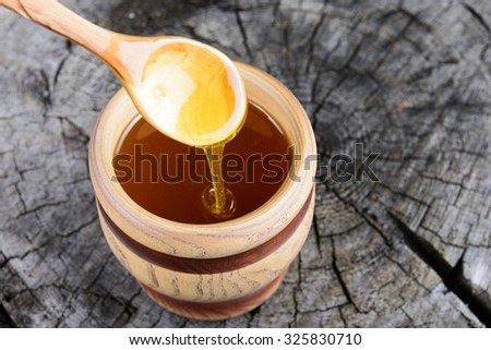 jar of honey and spoon with honey on a wooden background - stock photo