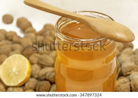 Jar of honey and spoon with lemon and walnuts
