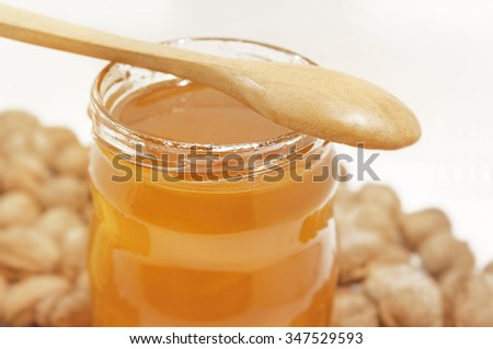 Jar of honey and spoon with walnuts on white